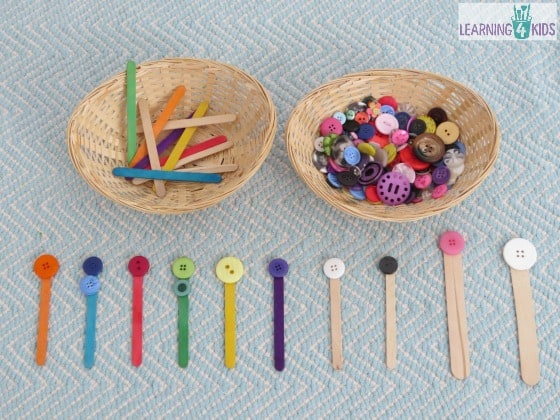 Invitation to play with buttons and pop sticks