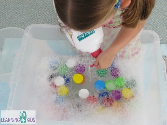 invitation to play sensory experience with bubble and bottle tops