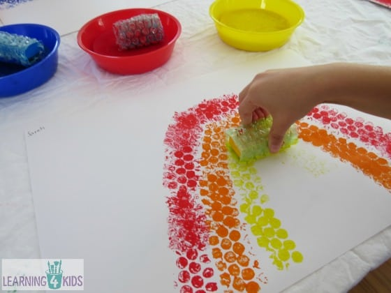 Painting a rainbow with bubble wrap covered blocks by learning 4 kids