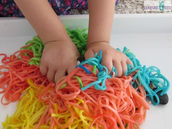 Bucket of colourful spaghetti worms sensory play for F crafts for toddlers