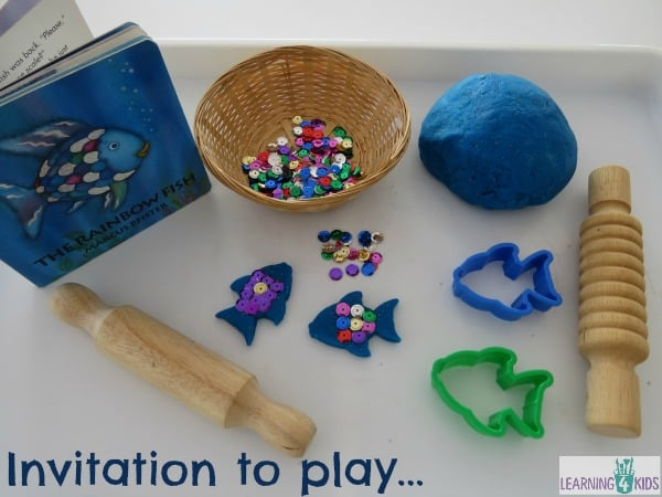invitation to play with the rainbow fish story book and play dough with sequins