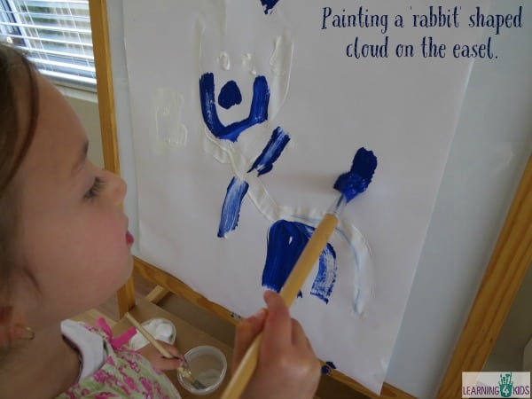 Painting a rabbit shaped cloud on the easel. Easel art inspired by Little Cloud by Eric Carle