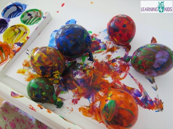 Painting with Balloons - rolling balloons around in paint on paper in a tray