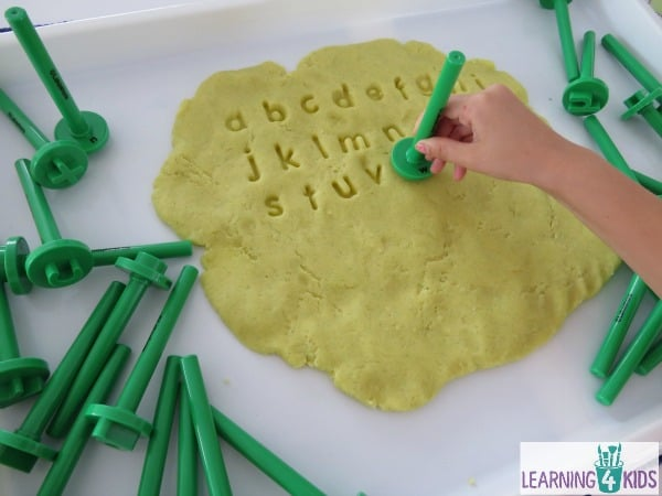 Learning the alphabet, using play dough as a canvas to create letter prints